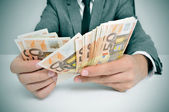 Man in suit with counting euro bills — Stock Photo