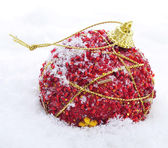 Red and golden christmas ball on the snow — Stock Photo