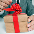 Man in suit opening a gift — Stockfoto
