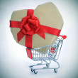 Heart-shaped gift in a shopping cart — Stock Photo