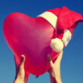 Heart-shaped balloon with a santa hat — 图库照片