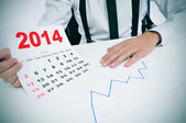 Man in suit with a chart and a 2014 calendar — Stock Photo