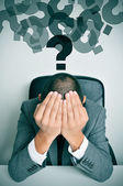 Businessman with his hands in his head and question marks — Stock Photo