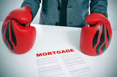 Man in suit with boxing gloves and a mortgage contract — Stock Photo