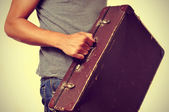Young man with old suitcase — Stock Photo