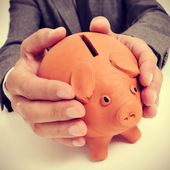 Man in suit with a piggy bank — Stock Photo