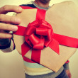 Young man with a heart-shaped gift — Stock Photo