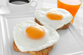 Heart-shaped fried eggs, bread and orange juice — Stock Photo