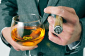 Man in suit with a cigar and a glass with brandy — Stock Photo
