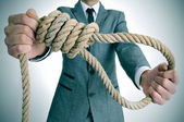 Man in suit holding a rope with a hangmans noose — Stock Photo