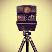 Old instant camera in a tripod — Stock Photo