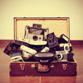 Old cameras in an old suitcase — Stock Photo
