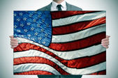 Man in suit holding an american flag — Stock Photo
