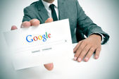 Uomo d'affari tenendo un cartello con la home page di google search — Foto Stock
