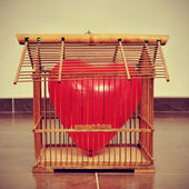 Heart-shaped balloon in an old birdcage, with a retro effect — Stock Photo