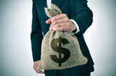Businessman with a burlap money bag — Stock Photo
