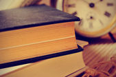 Old books and an old alarm clock, with a retro effect — Stock Photo