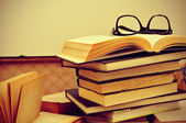 Books and eyeglasses in an old suitcase, with a retro effect — Stock Photo