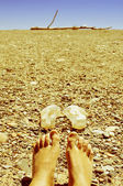 Bare feet in a shingle beach — Stock Photo