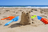 Sandcastle and toy shovels on the sand of a beach — Stock Photo
