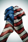 Man clasped hands patterned with the american flag — Stock Photo