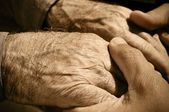 Young man holding the hands of an old man — Foto Stock