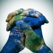 World map in the clasped hands of a man (Earth map furnished by  — Stock Photo #47489517