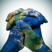 World map in the clasped hands of a man (Earth map furnished by  — Stock Photo