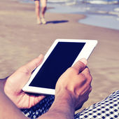 Man using a tablet or an e-book on the beach, with a retro effec — ストック写真