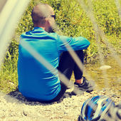 Cyclist getting some rest at the riverside with a retro filter e — Stock Photo