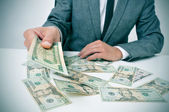 Man in suit giving dollar bills — Stock Photo