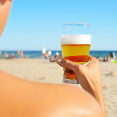 Young man having a refreshing beer on the beach — Stock Photo