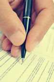 Man hand with a pen, with a retro filter effect — Stock Photo