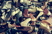 Second hand shoes in a flea market, with a retro filter effect — Stock Photo