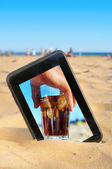 A tablet on the sand of a beach — Stock Photo
