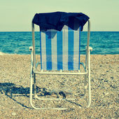 Deckchair and man swimsuit on the beach, with a retro effect — Zdjęcie stockowe