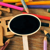 Blank chalkboard label and colored pencils on a rustic wooden ba — Stock Photo