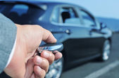Man in suit opening his car with the control remote key — Stock Photo