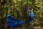 Young fairy woman flying up in forest — Stock Photo