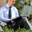 Working with laptop in a park — Stock Photo