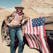 Young cowgirl with american flag — Stock Photo