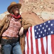 Young blond cowgirl with american flag — Stock Photo