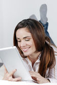 Smiling woman on sofa with tablet — Stock Photo