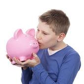 Cute boy kissing pink piggybank — Stock Photo