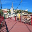Red footbridge on Saone river and church — Stock Photo