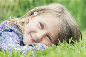 Girl lying on grass smiling — Stock Photo