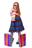 Happy fashion little redhead girl with shopping bags. — Stock Photo