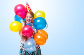 Happy little girl with balloons on blue background — Stock Photo