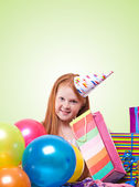 Happy party redhead girl with balloons and gift box on green ba — Stock Photo
