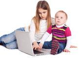 弟弟和妹妹使用便携式计算机 — 图库照片